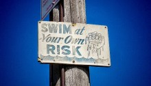 """""""Swim at your own risk"""" sign nailed to post"""