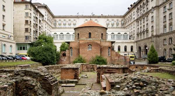 """he Church of St George (??????? """"????? ??????"""" or Rotonda """"Sveti Georgi"""") is an Early Christian red brick rotunda that is considered the oldest building in Sofia, the capital of Bulgaria. The rotunda has a diameter of 9.5m and is about 14m high. It's brick walls are an impressive 1.40m thick. The building is situated amid remains of the ancient town of Serdica.  Built by the Romans in the 4th century CE, it is mainly famous for the 12th-14th century frescoes inside the central dome. Three layers of frescoes have been discovered, the earliest dating back to the 10th century. Magnificent frescoes of 22 prophets over 2 metres tall crown the dome.   The original function of the rotunda is still debated. Some say it was built as a bath (or kaldarium), others argue that since it was located in the centre of 2nd century AD Roman public buildings, it likely had a religious and ceremonial function. Emperor Constantine the Great turned the Rotunda into a Christian temple, which surived until the invasion of Attila's Huns, when it was almost completely destroyed. It was reconstructed during the reign of Emperor Justinian.  During the reign of sultan Selim I (16th century), the church was turned into a mosque, the 'Gyul Mosque'. A minaret was constructed, and the Early Christian art was painted over with Islamic decorative elements.  The original frescoes (3 layers) were only uncovered during restoration works in the 20th century."""