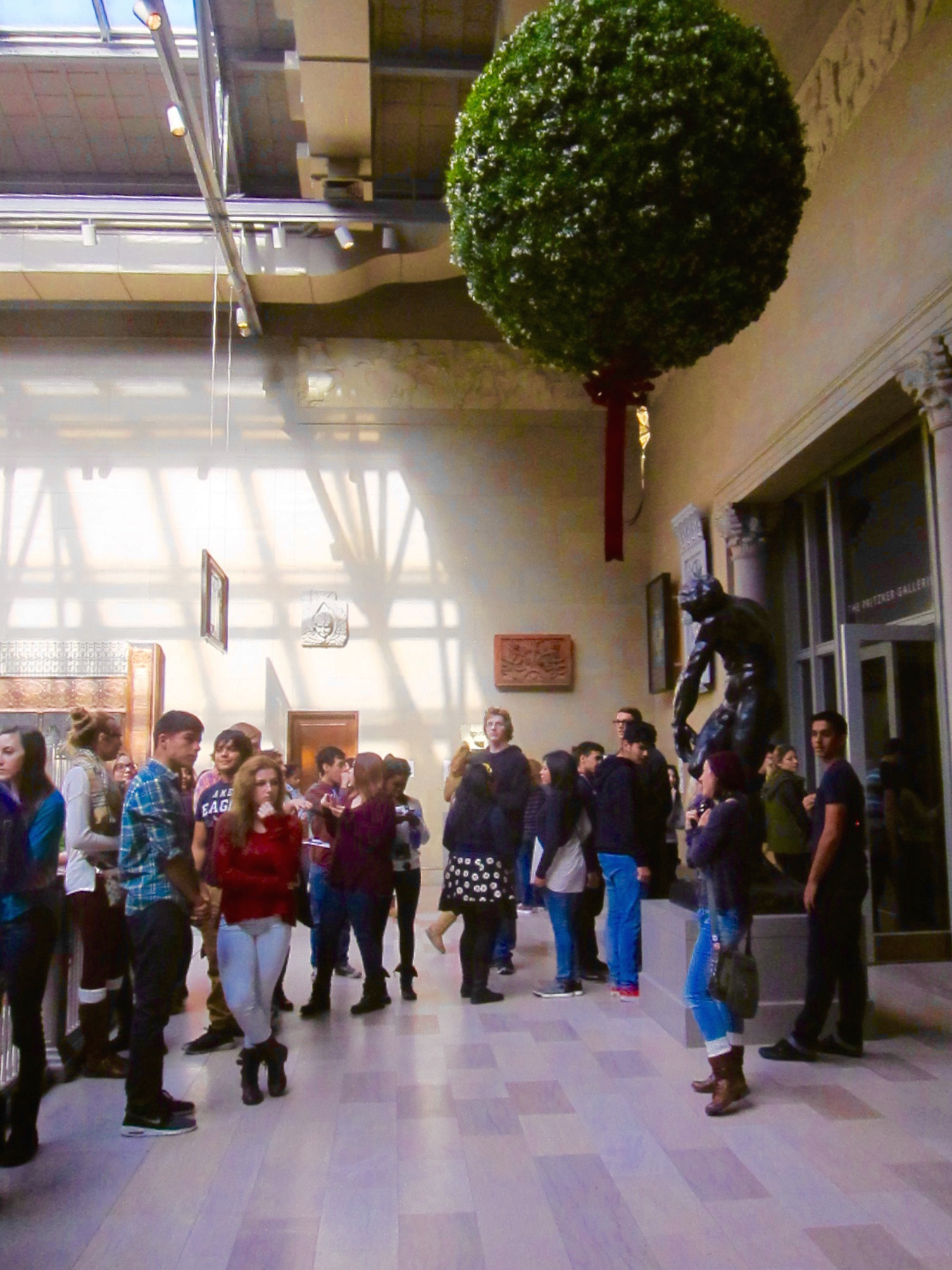 Teens studiously avoiding an enormous mistletoe at a major Chicago museum.
