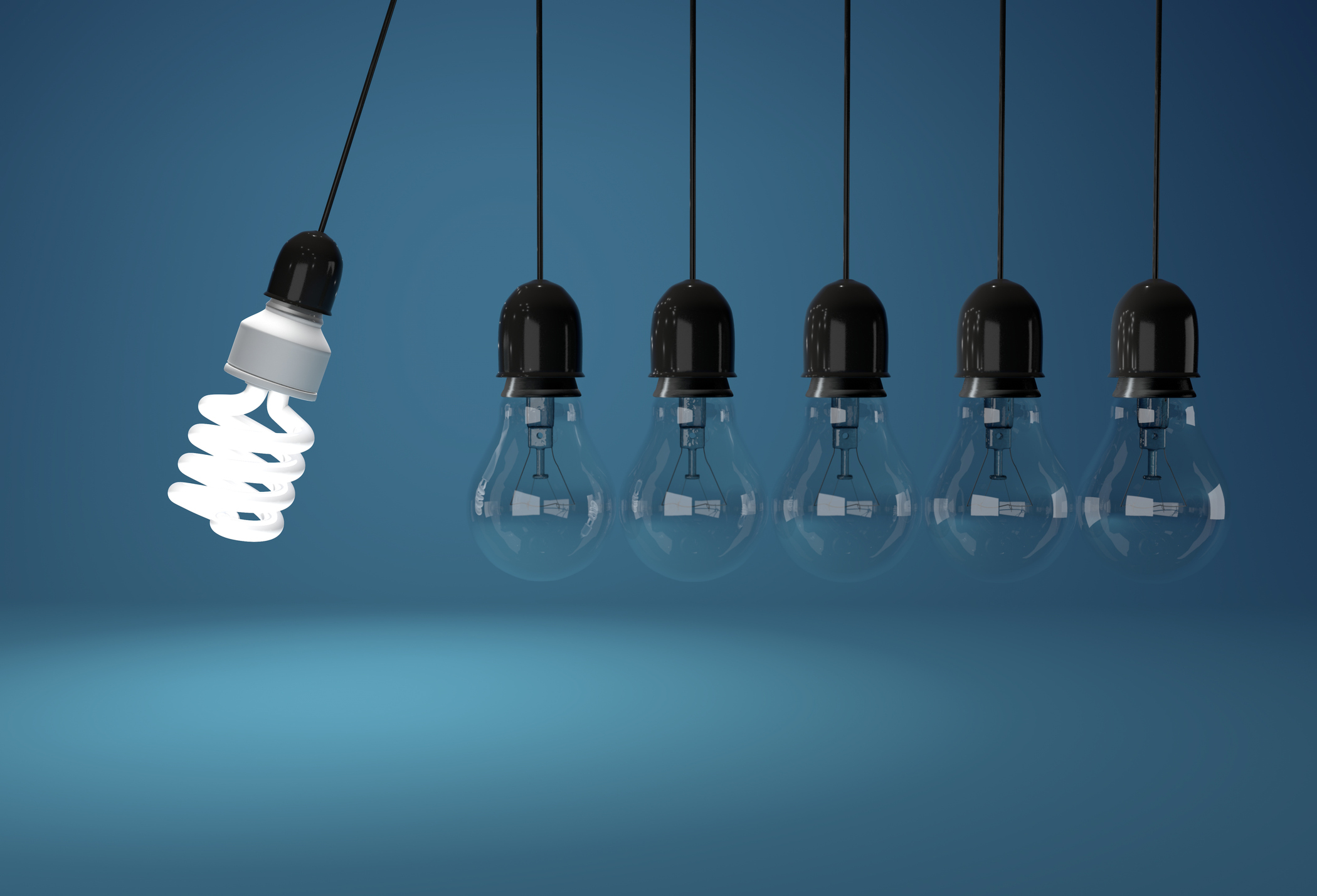 Energy saving bulb and incandescent bulb in perpetual motion over blue background