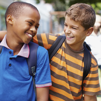 Two boys in their school playground having a good laugh together - copyspace