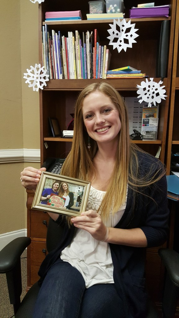 Family Support Coordinator, Brooke Larson, poses with her photo from the Shop for Mom event, coordinated by Hillside UMC on 12/6/15