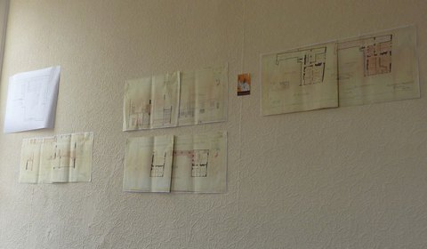 Our breakroom wall - building plans from 1937 and a picture of the Pope we found lying around
