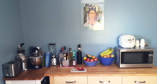 A view of my ikean kitchen counter with strawberries and Frida Kahlo looking down from above.