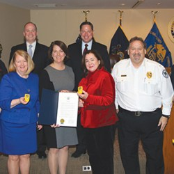 Delaware County Council and the Department of Intercommunity Health partnered with the family of the late Dr. Fritz Gallagher to supply all Emergency Medical Service providers with personal carbon monoxide detectors to warn them of high levels of CO when responding to a call. Shown at the County Council meeting are (from left), Jody Rioboli and Brian Zimmerman, Radnor Fire Co. EMS; Maureen Hennessey, director of Intercommunity Health and Regional EMS; Councilwoman Colleen Morrone; Casey Gallagher, widow of the late Fritz Gallagher; Robert Reeder, president, Delaware County Emergency Health Services Council; Kevin Daley, Tinicum Fire Co. EMS; and (back row), Councilmen John McBlain and Dave White.