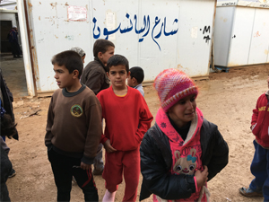 Children playing outside the SAMS headquarters in Zaatari. The street name meaning 'Anise Street' is written on the wall behind them.