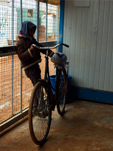 A child waits by his bicycle at the SAMS clinic gates.