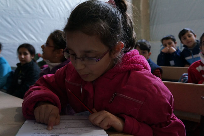 Children attend a remedial class, held inside a building sheltering displaced families in Homs. The classes are run in four shifts daily, providing children aged 4–12 years with lessons in Arabic and mathematics, as well as with recreational activity. © UNICEF/NYHQ2013-0130/Morooka