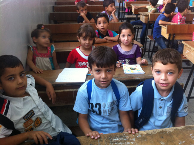 Children study English during a remedial education class at a UNICEF-supported school club in Dara'a city. © UNICEF Syria/2013/Kanawati