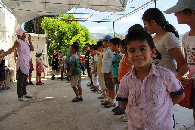 Displaced children participate in a game that teaches concentration skills as part of psychosocial activities at a centre in rural Tartous.   © UNICEF Syria/2013/Hassoun