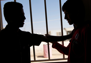 Hussein (name changed), 16, and another unaccompanied child at Za'atari camp. Hassan's older brother has been located at the camp, and social workers are finalizing the reunification process. © UNICEF Jordan/Noorani