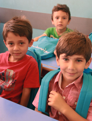 Children at a primary school in Rural Damascus are happy to receive UNICEF school bags containing station items including notebooks, pens, and colouring pencils. ©UNICEF Syria-2013/Halabi