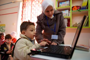 A teacher helps a young student use a laptop.