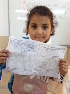 7-year old Tac Ismail receives her first ever school report at a UNICEF built school in Islayihe, Turkey. ©UNICEF/Turkey-2014/Yurtsever