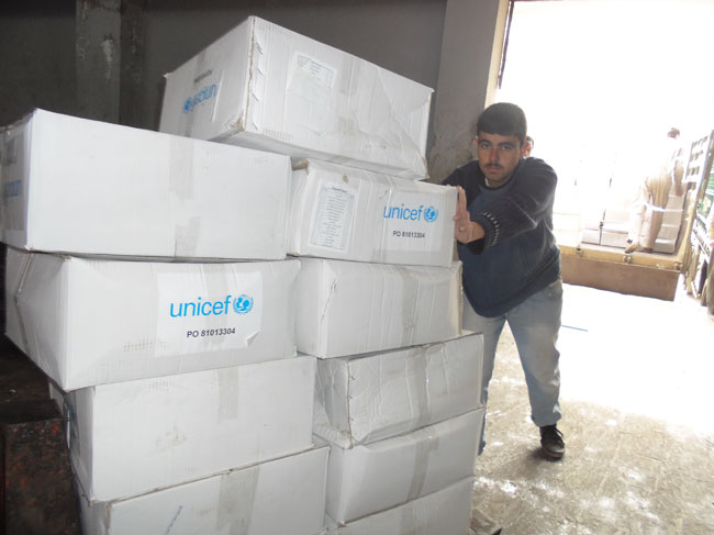 A worker moves UNICEF family hygiene kits from a truck into a warehouse at Areha. ©UNICEF/Syria-2014/Kaae