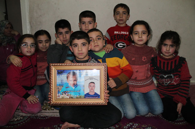 8-year old Norah (right), 11 siblings and their parents live in a one-room house in Nizip, Turkey. The children hold a picture of two family members they lost in Syria. © UNICEF/Turkey-2014/Jansen