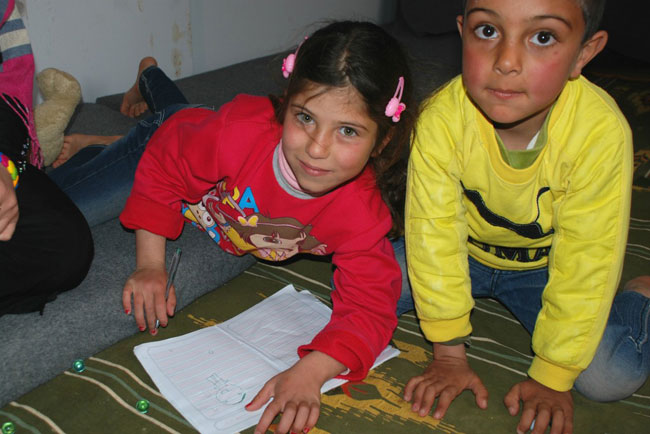 رنيم (يسار) ترسم مع شقيقها في الكرفان الذي تسكن فيه مع أسرتها في مخيم الزعتري للاجئين في الأردن