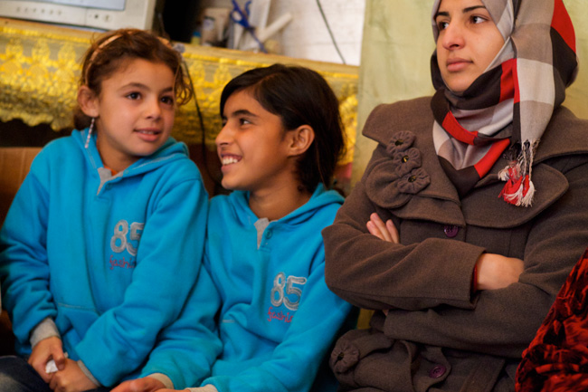 18-year old Huda (right) sits with her siblings in their tent at an informal settlement in Lebanon. ©UNICEF/Lebanon-2013/Noorani