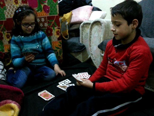 سيدرا وشقيقها أحمد يلعبان الورق في ملجئهم. العائلة ليس لديها أسرّة، ولذا فهم ينامون على فرشات على الأرض.