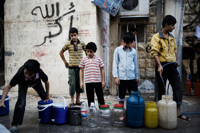 Children line up to collect water from a UNICEF-supported water tanker in Hama governorate. © SARC/2013