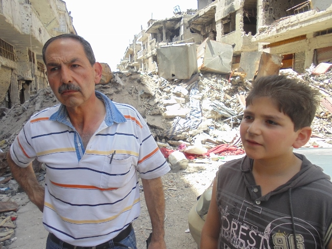 A father and son outside their destroyed home in the Old City of Homs. The family was displaced by fighting and have only been able to return recently with the cessation of hostilities in the area. © UNICEF/Syria-2014Tiku.