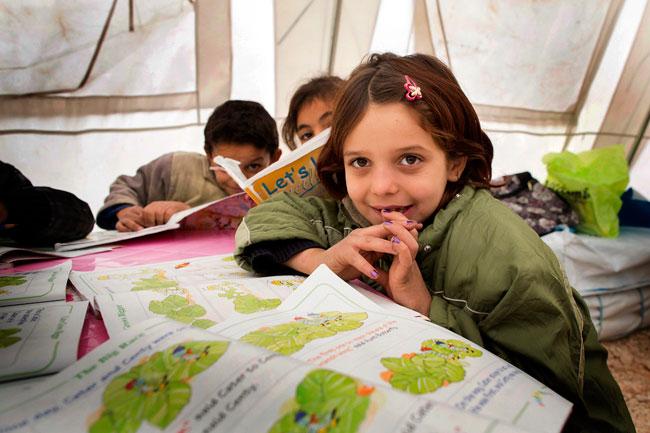 Children read in the centre at Faida tented settlement in Lebanon. © UNICEF/Lebanon-2014/ Brunetti