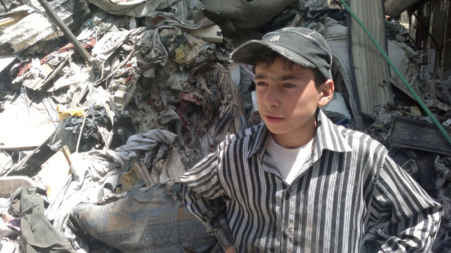 إباء (13 سنة) يقف بجانب كومة من الركام التي يبحث فيها عن قطع البلاستيك والمعدن ليبيعها في السوق