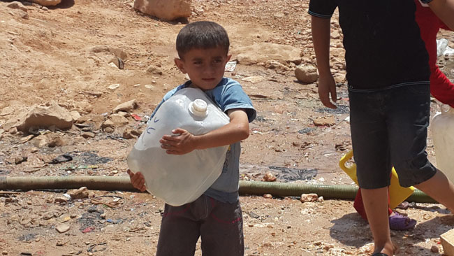 Young children spend long hours queuing at the shelter's water distribution point. © UNICEF Syria/2014/Kumar Tiku