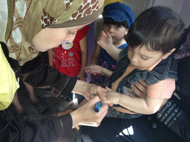 A health worker in Qudsiya, Syria marks the finger nail of a young child to show that she has received a dose of polio vaccine. Families were lining up at the health centre to have their under-five children vaccinated.  ©UNICEF/Syria-2014/Saeed