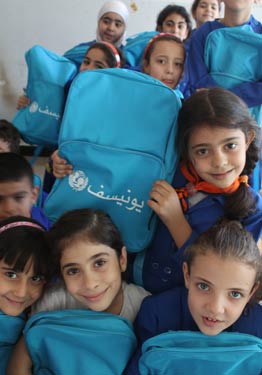 © UNICEF Syrian Arab Republic/2014/Rashidi Third grade students happily display their new bags at a school in central Damascus. With the support of the EU, UNICEF is providing education supplies to more than a million Syrian children.