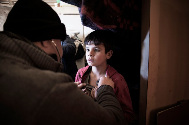 A doctor sees a child patient at Refugee Camp 29 in the Bekaa Valley. UNICEF-funded mobile medical units have been working to ensure that Syrian refugees stranded by harsh winter conditions get basic medical assistance. ©UNICEF/Lebanon-2015/Romenzi
