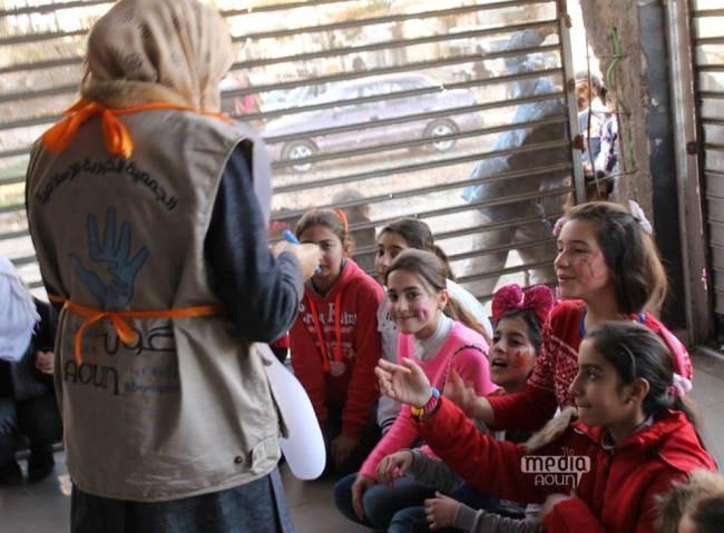 متطوع شاب يعمل مع مجموعة من الفتيات النازحات في واحدة من جلسات نشاطات اليوم المفتوح التي تدعمها عون/ اليونيسف في حي الإنشاءات في حمص. ضمت هذه الجلسة 389 طفل، منهم 209 فتيات ©UNICEF/Syria/2015/Aoun/Ghadeer Qara Bolad