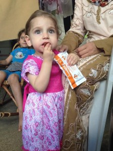 Pic 2©UNICEF Syria/2015/Saker- Farah grasping her ready-to-use food supplement, given to her at the UNICEF- supported medical center as part of her treatment.