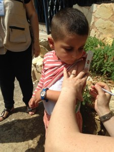 Pic 3©UNICEF Syria/2015/Saker- Community outreach volunteers tour rural Lattakia daily to identify and prevent cases of malnutrition.4 year old Mohammad patiently observes as a volunteer measures the circumference of his upper-arm, a measure that helps determine if he's malnourished.