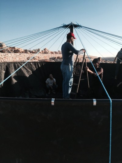 """©UNICEF Syria/2015- Workers install a UNICEF-supported water tank in Idleb. Before the installation of the tanks, families in collective shelters had to spend long hours every day lining up to collect water trucked from other areas. """"We faced many obstacles,"""" said Michele Al- Kaae, UNICEF Emergency Officer. """"In May of this year, the suddenly-changing security situation made Idleb completely inaccessible. This in return interrupted the whole system we had previously established to deliver services in the governorate. It took us more than two months of deliberations, coordination with implementing partners and great efforts by our field facilitator to rebuild the system and reach the vulnerable populations."""" The intense heat wave, along with the lack of access, exasperated living conditions and called for quick action."""