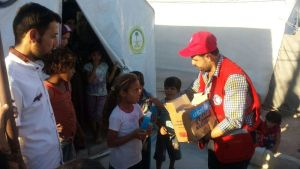 ©UNICEF Syria/2015- A Syrian Arab Red Crescent (SARC) volunteer distributes lice shampoo provided by UNICEF to children at an IDP shelter in Harim, Idleb. The heat wave, combined with lack of water and scarce access to hygiene tools has resulted in the reporting of many cases of lice infestation among children. 21.000 bottles of lice shampoo were distributed to more than 10,500 families across the governorate.