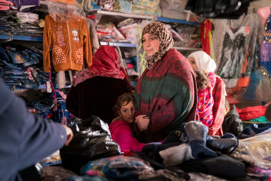 Manar selecting winter clothes with her children at a shop in Za'atari camp.  Photo: unicefjordan/herwig