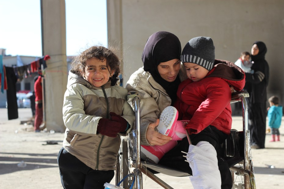 © UNICEF Syrian Arab Republic/2016/Al-Issa Five-year-old Rahaf and her two-year-old brother Wael sit happily by their mother in their new winter clothes. They are among the tens of thousands of children who fled the intense ongoing fighting in eastern Aleppo.