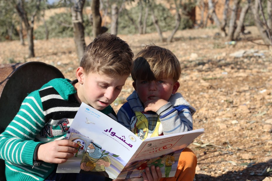 "©UNICEF/Syria/2017/Al-Issa Amin, 10, (left) uses an educational magazine distributed by UNICEF-supported volunteers to explain to his 3 year-old brother the different shapes of unexploded remnants of war. ""I'm so lucky to not have been killed or lost a body part,"" said Amin. ""All children should know the risks of these objects and to stay away from them."""