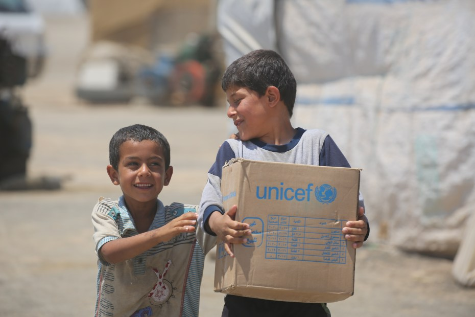 ©UNICEF/ Syria 2017/ Delil Souleiman Children carry a newly-distributed family hygiene kit in Al- Karama makeshift camp in Ar-Raqqa.  UNICEF is distributing hygiene kits to protect children against waterborne diseases, as well as nutritional supplies and micronutrients for children and pregnant and lactating women.
