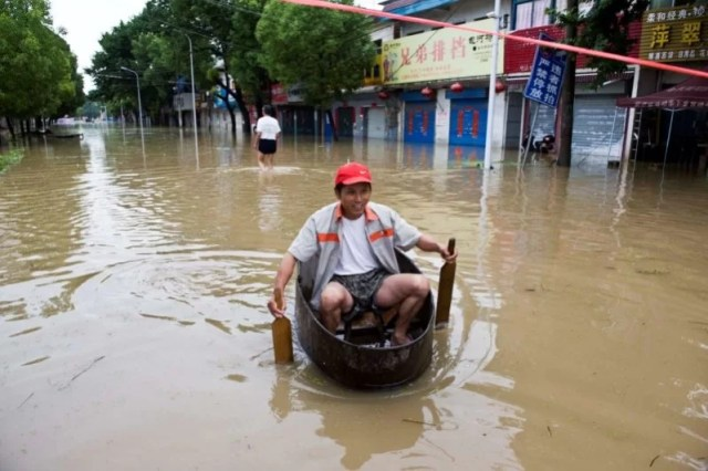 A resident rows a makeshift boat to make his way at a flooded street in Chaohu, Anhui Province, China, July 2, 2016. Picture taken July 2, 2016. China Daily/via REUTERS