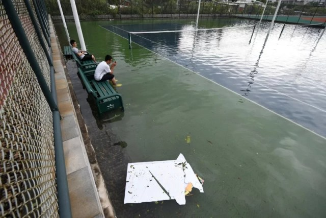 People sit on bench inside a flooded tennis court after Typhoon Meranti makes a landfall on southeastern China, in Xiamen, Fujian province, China, September 15, 2016. REUTERS/Stringer