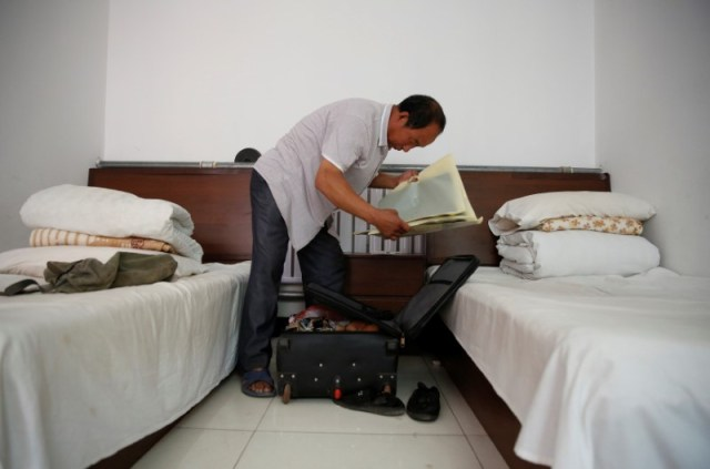 Pan packs his suitcase as he prepares to check out of the accommodation where some patients and their family members stay while seeking medical treatments in Beijing, China, June 23, 2016. REUTERS/Kim Kyung-Hoon