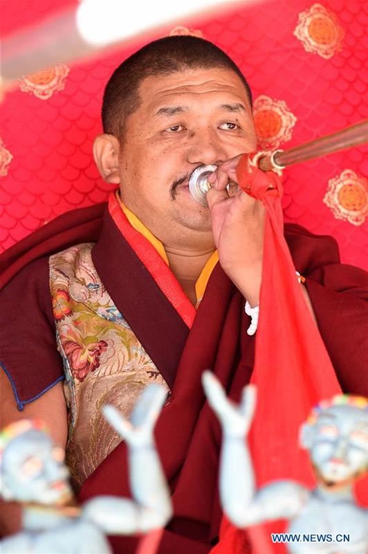 A lama blows a religious horn