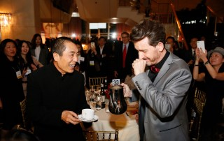 From right, Emcee Jeff Locker fulfills a dream to pour Zhang Yimou, Director and Lifetime Achievement Award winner a cup of coffee during the 2015 Asia Society U.S.-China Film Summit and Gala held at the Dorthy Chandler Pavilion on Thursday, November 5, 2015, in Los Angeles, Calif. (Photo by Ryan Miller/Capture Imaging)