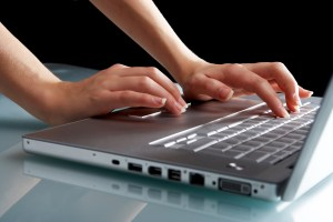 Hands typing on a laptop