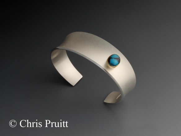 Textured, sterling silver, tapered, anticlastic bracelet with 18k gold bezel and raised Bisbee turquoise