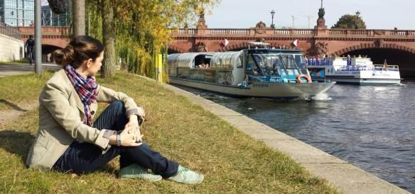 Frau sitzt am Ufer der Spree und schaut Ausflugsbooten zu
