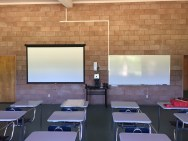 """Before, my classroom had faced the East, meaning that 1) it was a very LONG classroom (read: hard to """"reach"""" all students) and 2) it had a ginormous window facing the left of my students (read: distraction factory). Now, things are turned so the front faces the South, and my projector has been ceiling mounted, pointing to a beautiful new pull-down screen that is DIFFERENT than the whiteboard, allowing me to show videos, images, resources AND utilize the whiteboard."""