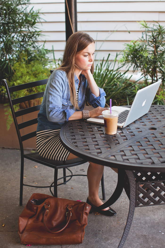 Graphic Designer with MacBook Pro and Coffee In Courtyard
